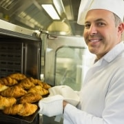 baker getting pastries out of the oven
