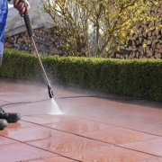 man cleaning walkway with power washer